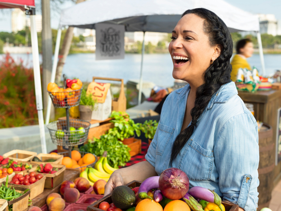 Woman enjoying herself while shopping at an outdoor farmers market.